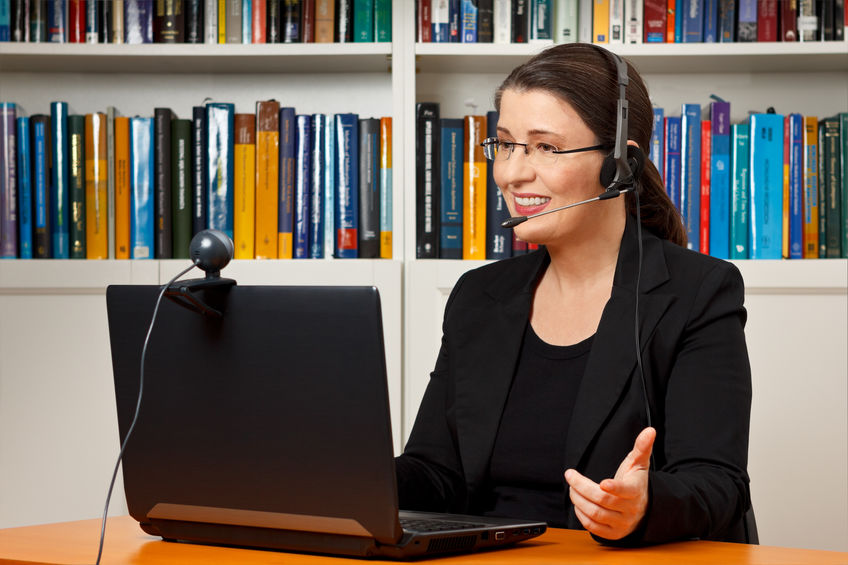 Woman wearing a headset conversing through a laptop with a webcam